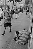 Pedestrians and elderly woman with mental health problems sleepinng rough on Euston Road, opposite Kings Cross station, London 1990.