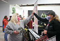 Tara Cody of Bentonville(from left) and Susan Oldfather of SeneGence high-five as they discuss wedding makeovers, Sunday, February 22, 2021 at the Benton County Fairgrounds in Bentonville. Wedding service providers showcased their services to the public including formal wear, music, photography, catering and makeovers. Check out nwaonline.com/210222Daily/ for today's photo gallery. <br /> (NWA Democrat-Gazette/Charlie Kaijo)