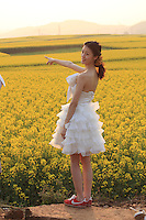 A young tourist from the city in a rape field.