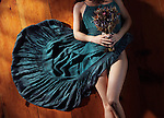 Sensual artistic abstract portrait of a woman in a bohemian blue dress with bare legs lying on the floor with a bouquet of wild flowers Image © MaximImages, License at https://www.maximimages.com