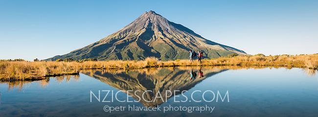 Hikers with Taranaki, Mt. Egmont with reflections in alpine tarn, Egmont National Park, North Island, New Zealand, NZ
