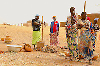 In Burkina Faso all the women spend a large part of the day grinding mile in wood basket