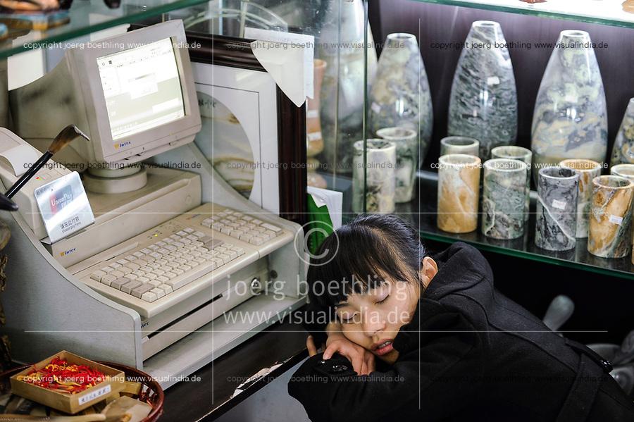 CHINA Province Yunnan, Kunming, airport , sleeping shop assistent