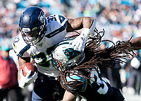 CHARLOTTE, NC - DECEMBER 15: Tre Boston #33 of the Carolina Panthers attempts to tackle Chris Carson #32 of the Seattle Seahawks who scores a touchdown during a game between Seattle Seahawks and Carolina Panthers at Bank of America Stadium on December 15, 2019 in Charlotte, North Carolina.