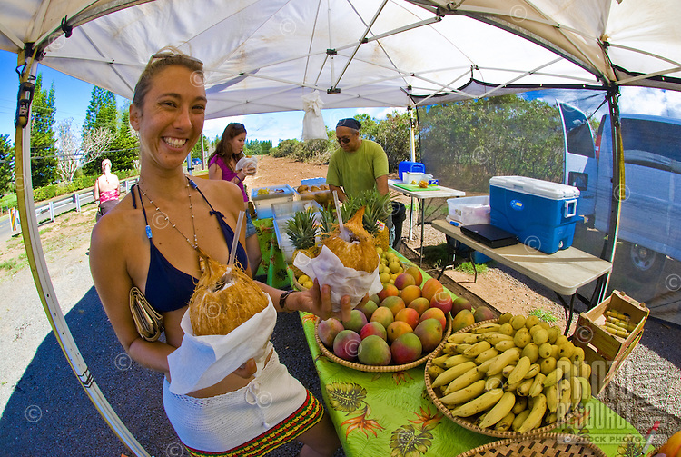 Young woman holding fresh, cold coconuts at a North Shore fruit stand in Haleiwa