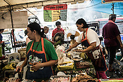 A shop sells different kinds of grilled fish, mostly tuna at the organic farmers market in Sacedo Park in Makati, Manila in the Philippines. There is a surge in the demand for organic products to supply for people who can afford to pay extra.<br /> Photograph: Sanjit Das/Panos for Greenpeace