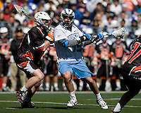 Michael Kimmel (15) of Johns Hopkins is checked by John Cunningham (3) of Princeton during the Face-Off Classic in at M&T Stadium in Baltimore, MD