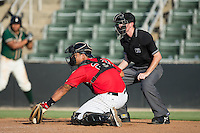 Kannapolis Intimidators catcher Daniel Gonzalez (23) reaches for a pitch in the dirt as home plate umpire Tyler Jones looks on during the game against the Greensboro Grasshoppers at Intimidators Stadium on July 17, 2016 in Greensboro, North Carolina.  The Grasshoppers defeated the Intimidators 5-4 in game two of a double-header.  (Brian Westerholt/Four Seam Images)