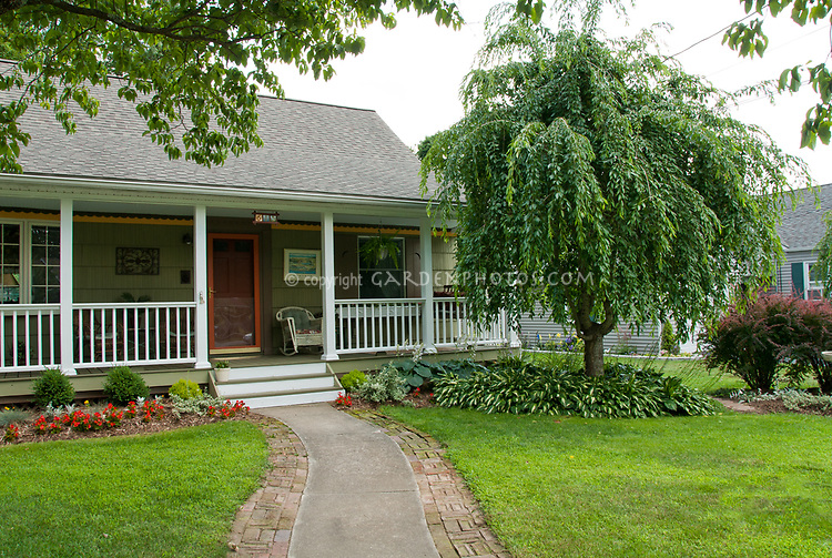 Front house entry curb apeal with pretty tree, lawn grass, front porch, flowers, widening a concrete border with bricks