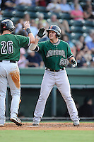 Second baseman Jeremy Sy (20) of the Augusta GreenJackets is congratulated by Ty Ross after scoring a run in a game against the Greenville Drive on Friday, July 11, 2014, at Fluor Field at the West End in Greenville, South Carolina. Greenville won, 7-6. (Tom Priddy/Four Seam Images)
