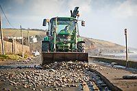 Friday 03 January 2014<br /> Pictured: A tractor clears debris  from the road in Amroth, West wales, damaged by the sea during a mix high tides and stormy weather.<br /> Re: Storm force winds and some of the highest tides in decades hit Wales early on Friday.
