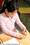 Education Elementary school Grade 5 class with science specialist making models from toothpicks and mini marshmallows female student working by herself vertical