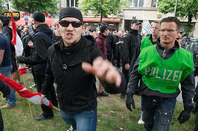 """Etwa 70 bis 80 Neonazis von den Autonomen Nationalisten und der NPD versuchten am Samstag den 14. Mai 2011 in Berlin Kreuzberg eine Demonstration unter dem Motto """"Wahrheit macht frei"""" zu veranstalten. Zu der Demonstration waren Neonazis aus Niedersachsen, Brandenburg und Nordrhein Westfalen angereist. Die Demonstration und die Demonstrationsroute wurde in Zusammenarbeit mit der Polizei geheim vorbereitet. Dennoch gelang es mehr als 800 Menschen die Demonstration mit Blockaden zu verhindern. Die Neonazis wurden von der Polizei in die U-Bahn geleitet, wo sie unter den Augen der Polizei Auslaender verpruegeln konnten.<br /> Im Bild: Ein Neonazi greift die Presse an. Der Polizeibeamte rechts weigerte sich eine Anzeige aufzunhemen und behauptet die Presse wuerde die Neonazis halt provozieren und dann passiert das eben.<br /> 14.5.2011, Berlin<br /> Foto: Christian-Ditsch.de<br /> [Inhaltsveraendernde Manipulation des Fotos nur nach ausdruecklicher Genehmigung des Fotografen. Vereinbarungen ueber Abtretung von Persoenlichkeitsrechten/Model Release der abgebildeten Person/Personen liegen nicht vor. NO MODEL RELEASE! Don't publish without copyright Christian-Ditsch.de, Veroeffentlichung nur mit Fotografennennung, sowie gegen Honorar, MwSt. und Beleg. Konto:, I N G - D i B a, IBAN DE58500105175400192269, BIC INGDDEFFXXX, Kontakt: post@christian-ditsch.de]"""