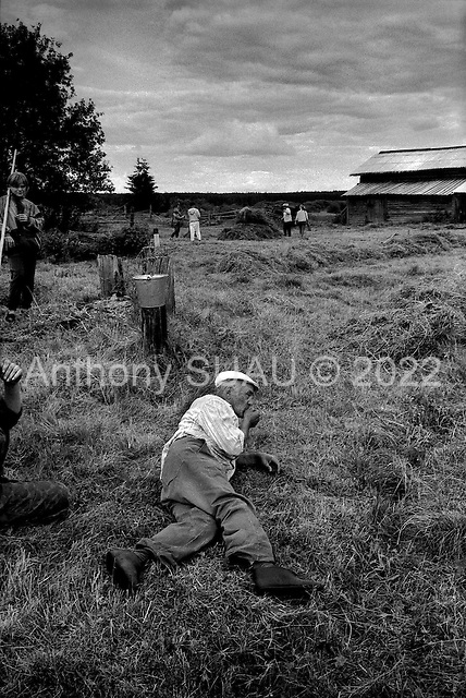 Kerga, Russia  .1998.Farmers cut and stack hay in an abandoned village..