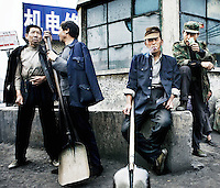 Coal workers smoke as they wait for work in central Taiyuan.