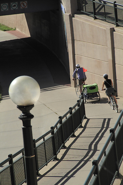 Parents riding bikes and pulling a baby carriage in Denver, Colorado. .  John offers private photo tours in Denver, Boulder and throughout Colorado. Year-round.