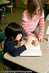 Education Elementary school Grade 1 mathematics hands on learning two female students gluing colored squares of paper as a measurement vertical