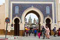 Fes, Morocco.  Women in Traditional Djellabas leaving Fes El-Bali (Old City) through the Bab Boujeloud.  The minaret of the Bou Inania medersa is in the background.