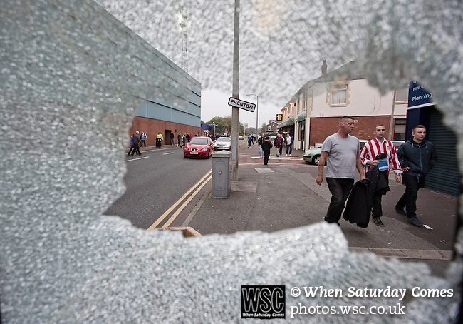 Tranmere Rovers 0 Stoke City 2, 25/09/2013. Prenton Park, Captial One Cup Third Round. Fans making their way towards the ground as seen through the shattered glass of a telephone box outside Prenton Park before Tranmere Rovers host Stoke City in a Capital One Cup third round match. The Capital One cup was formerly known as the League Cup and was competed for by all 92 English Premier League and Football League clubs. Visitors Stoke City won the match 2-0, watched by a crowd of 5,559 spectators. Photo by Colin McPherson.