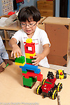 Education preschool 3-4 year olds boy building and playing with colorful plastic connecting bricks talking to himself