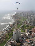 Deddeda flies her paraglider above the coastal cliffs and skyscrapers in the district of Miraflores, Lima, Peru.