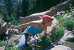 A young woman stops to smell a blue columbine (Aquilegia coerulea) while hiking in Rocky Mtn Nat'l Park, CO