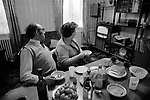 Jewish family at home north London watching TV in their dinning room cum living room. 1970s UK. The table has been laid out for an evening meal and is now all but over. The Goodman family at home, Mr David,  Goodman, always known a Lou, was a taxi driver based in Manor House, 1970s UK.