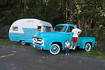 Two kids hanging out on a SS Ford F-100 223 Inline 6. The sea foam green is the vehicle's original color. Next to the Ford is a 13-foot 1964 Serro Scotty travel tailer.