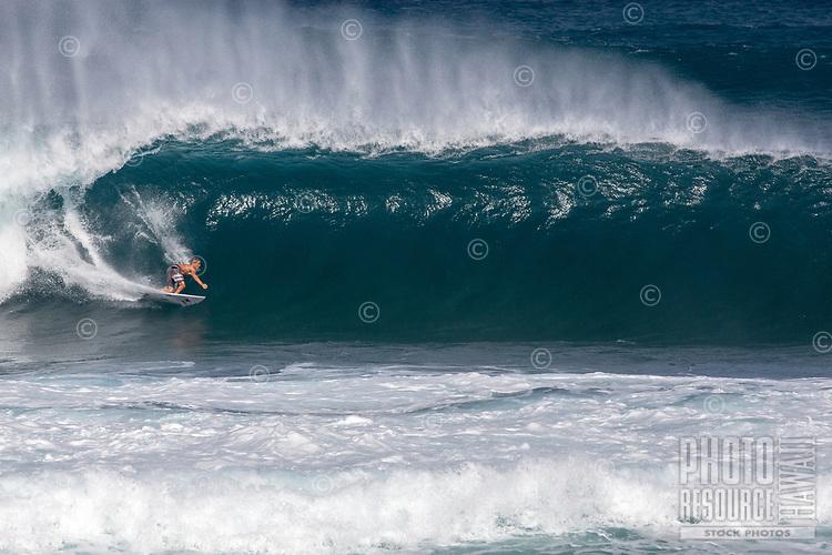 A surfer gets barreled  on a big wave at Pipeline (off of 'Ehukai Beach Park), North Shore, O'ahu.