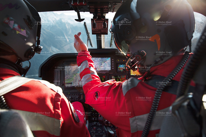 """Switzerland. Canton Grisons. Bondo.On board of a  Rega Agusta AW109 SP Grand """"Da Vinci"""" helicopter. The pilot Silvio Pini (R) talks to the paramedic Giovanni Beldi (L) during a flight over the Bregaglia valley. All Rega helicopters carry a crew of three: a pilot, an emergency physician, and a paramedic who is also trained to assist the pilot for radio communication, navigation, terrain/object avoidance, and winch operations. The name Rega was created by combining letters from the name """"Swiss Air Rescue Guard"""" as it was written in German (Schweizerische Rettungsflugwacht), French (Garde Aérienne Suisse de Sauvetage), and Italian (Guardia Aerea Svizzera di Soccorso). Rega is a private, non-profit air rescue service that provides emergency medical assistance in Switzerland. Rega mainly assists with mountain rescues, though it will also operate in other terrains when needed, most notably during life-threatening emergencies. The AgustaWestland AW109 is a lightweight, twin-engine, helicopter built by the Italian manufacturer Leonardo S.p.A. (formerly AgustaWestland, Leonardo-Finmeccanica and Finmeccanica). Leonardo S.p.A is an Italian global high-tech company and one of the key players in aerospace. In close collaboration with the manufacturer, the Da Vinci has been specially designed to cater for Rega's particular requirements as regards carrying out operations in the mountains. It optimally fulfills the high demands made of it in terms of flying characteristics, emergency medical equipment and maintenance. Safety, performance and space have been increased, and maintenance and noise emissions reduced. The ALPHA Eagle helicopter helmet is designed for use in commercial helicopters and fixed wing aircraft. ALPHA helmets are the world's leading aircrew helmets. The Val Bregaglia (Lombard: Val Bargaja, German: das Bergell ) is an alpine valley in the canton of Graubunden ( Grisons). 20.09.2017 © 2017 Didier Ruef"""