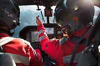 "Switzerland. Canton Grisons. Bondo.On board of a  Rega Agusta AW109 SP Grand ""Da Vinci"" helicopter. The pilot Silvio Pini (R) talks to the paramedic Giovanni Beldi (L) during a flight over the Bregaglia valley. All Rega helicopters carry a crew of three: a pilot, an emergency physician, and a paramedic who is also trained to assist the pilot for radio communication, navigation, terrain/object avoidance, and winch operations. The name Rega was created by combining letters from the name ""Swiss Air Rescue Guard"" as it was written in German (Schweizerische Rettungsflugwacht), French (Garde Aérienne Suisse de Sauvetage), and Italian (Guardia Aerea Svizzera di Soccorso). Rega is a private, non-profit air rescue service that provides emergency medical assistance in Switzerland. Rega mainly assists with mountain rescues, though it will also operate in other terrains when needed, most notably during life-threatening emergencies. The AgustaWestland AW109 is a lightweight, twin-engine, helicopter built by the Italian manufacturer Leonardo S.p.A. (formerly AgustaWestland, Leonardo-Finmeccanica and Finmeccanica). Leonardo S.p.A is an Italian global high-tech company and one of the key players in aerospace. In close collaboration with the manufacturer, the Da Vinci has been specially designed to cater for Rega's particular requirements as regards carrying out operations in the mountains. It optimally fulfills the high demands made of it in terms of flying characteristics, emergency medical equipment and maintenance. Safety, performance and space have been increased, and maintenance and noise emissions reduced. The ALPHA Eagle helicopter helmet is designed for use in commercial helicopters and fixed wing aircraft. ALPHA helmets are the world's leading aircrew helmets. The Val Bregaglia (Lombard: Val Bargaja, German: das Bergell ) is an alpine valley in the canton of Graubunden ( Grisons). 20.09.2017 © 2017 Didier Ruef"