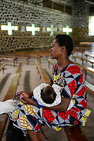 RWANDA, Ruhengeri, village Busogo, woman with baby praying a rosary in church / RUANDA, Frau mit Kleinkind in Kirche Busogo