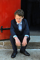 Boy in a suit and bow tie sitting on church steps.