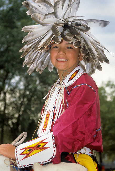 Teenage boy dressed in traditional mandan style feather headdress and beadwork.