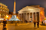 As evening falls, the bars around the plaza open and tourists mix with locals around the central fountain (the Fontana del Pantheo) in the Piazza della Rotonda, in front of the Pantheon in Rome, Italy.
