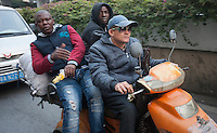 African and Chinese people are seen riding a motoerbike in an area of Guangzhou known to locals as 'Chocolate City', Guangzhou, Guangdong Province, China, 08 December 2014. The health authorities of Guangzhou are said to be stepping up their monitoring of the African community in light of the ongoing outbreak of the Ebola virus disease in West Africa.