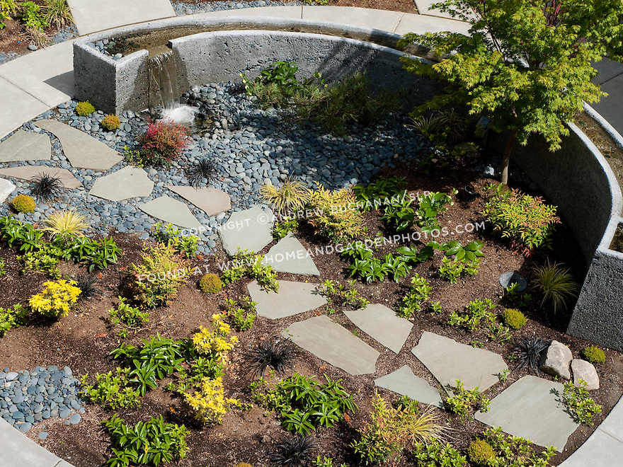 A stone path leads through the garden past a circular water feature.
