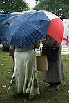 Barnet Gypsy Horse Fair Hertfordshire UK. Gypsy ladies chatting under their umbrellas.