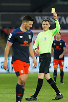 Referee Leigh Doughty (R) shows a yellow card to Tom Lockyer of Luton Town during the Sky Bet Championship between Swansea City and Luton Town at the Liberty Stadium, Swansea, Wales, UK. Saturday 05 December 2020