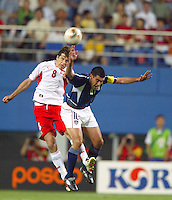Claudio Reyna collides with a Polish defender while battling for a header. The USA lost 3-1 against Poland in the FIFA World Cup 2002 in Korea on June 14, 2002.