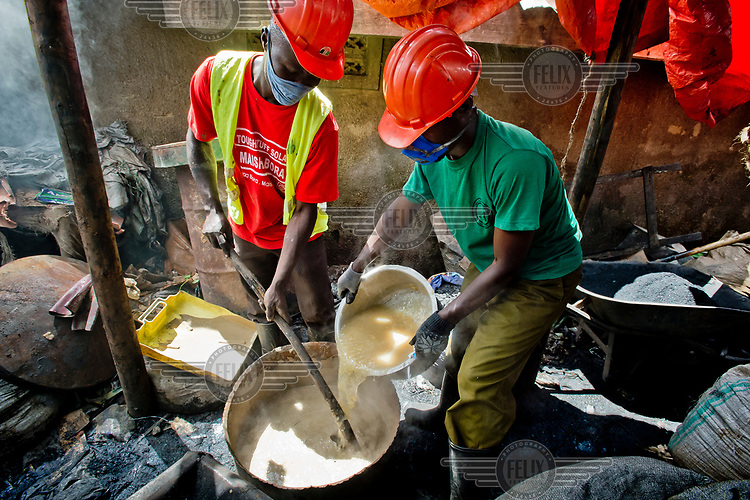 In a backyard workshop, members of the Lulana Communal Environmentalist group mix a binder for the briquettes, used as cooking fuel, an alternative to charcoal or wood, they manufacture from recycled or waste cardboard. LCE sells its briquettes to individuals and restaurants.