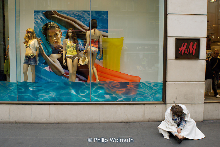 A disturbed man wrapped in a blanket begs outside a Hennes store in Oxford Street, London.