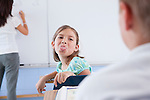 USA, Illinois, Metamora, Teacher and students (8-9) in classroom, girl showing tongue