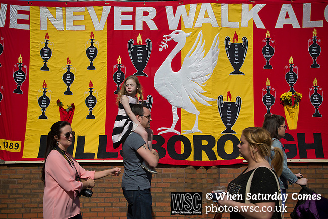 People walking in front of a banner commemorating the 1989 Hillsborough stadium disaster, before the 25th anniversary memorial service to the disaster at Liverpool Football Club's Anfield Stadium. The Hillsborough disaster led to 96 Liverpool football fans losing their lives in a crush at an FA Cup semi final tie against Nottingham Forest. The families of the victims campaigned against the original verdict of the incident and were rewarded with a new inquiry held in 2014 into events at the match at Hillsborough. Photo by Colin McPherson.