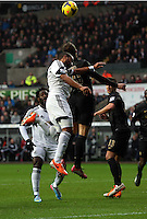 Wednesday, 01 January 2014<br /> Pictured L-R: Ashley Williams of Swansea is battling for a header against Edin Dzeko of Manchester City.<br /> Re: Barclay's Premier League, Swansea City FC v Manchester City at the Liberty Stadium, south Wales.