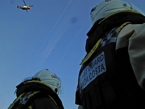 Irish Coast Guard officers with a rescue helicopter overhead