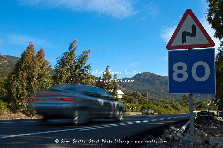Speeding car on highway next to speed limit sign, Andalusia, Spain.