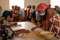 BURKINA FASO, Banfora, Association Wouol Bérégadougou factory Cashew production for export , women process Fairtrade Cashew nuts / BURKINA FASO, Banfora , Association Wouol Bérégadougou Fabrik zur Verarbeitung von Kaschunuessen , GIZ Projekt Wertschoepfungskette und Foerderung des landwirtschaftlichen Sektor , Frauen verarbeiten Fairtrade Cashew Nuesse