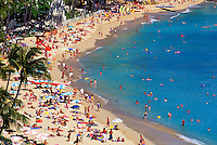 Famous Waikiki beach with many visitors lining the beach