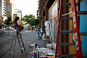 New York New York<br /> July 2, 2020<br /> <br /> Artists cover the last plywood windows on the lower Eastside at Bowery and East 4th street in Manhattan during the Black Lives Matters moment and coronavirus pandemic.